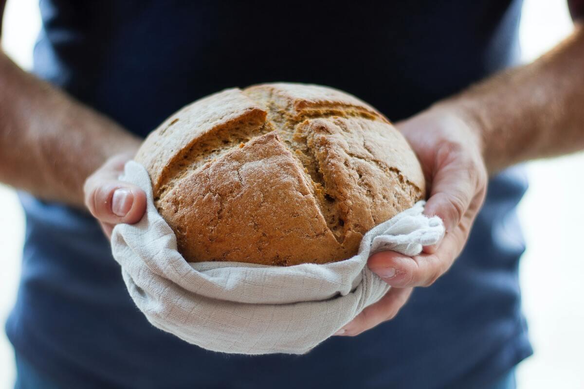 personne qui tient un pain devant elle.